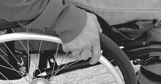 Hand clutching the wheel of a wheelchair